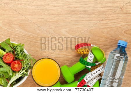 Dumbells, tape measure and healthy food over wooden background. Fitness and health. View from above with copy space