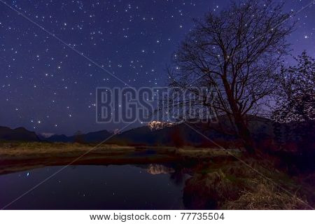 Bright Stars With Tree And Mountain Reflection