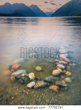 Colorful Rocks In Lake With Background Mountains