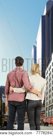 Young couple, arm in arm, looking at the bristle of New York during a city trip
