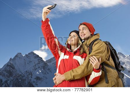 young couple taking a selfie during wintersports of a magnificent view over an alpine mountain rainge