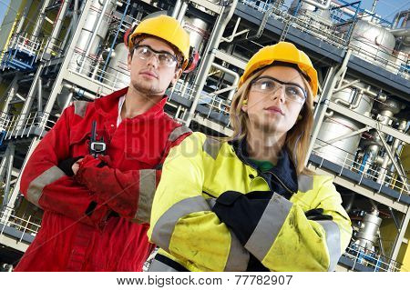 Two security engineers at their jobs, posing confidently in front of a large chemical installation with tanks, valves, tubes and safety structures