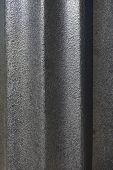 Retro-style steel light pole in a park.  Unusual fluted design with beautiful texture and charcoal gray paint.  Beautiful contrast of light and shadow. poster