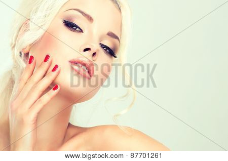 Beautiful blonde woman with retro hairstyle and red nail