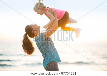 Mother Throwing Baby Up On Beach In The Evening