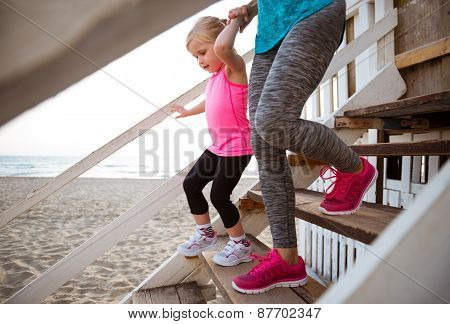 Healthy Mother And Baby Girl Walking Down The Stairs