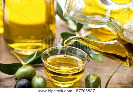 Olive Oil. Bottle pouring Virgin Olive Oil in a bowl close up. Olives and Healthy Olive oil being poured from glass bottle. Diet. Dieting concept. Healthy eating poster