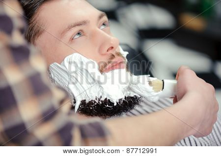 Client shaving at barber shop