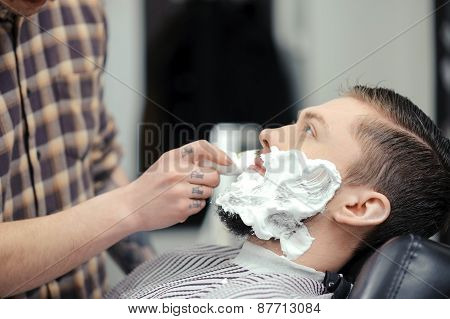 Shaving the beard. Barber putting some shaving cream on a client before shaving his beard in a barber shop poster