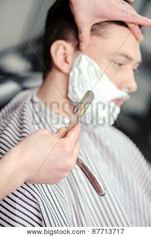 Client shaving at barber shop