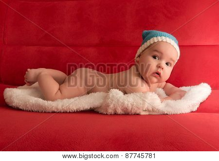 Baby In A Blue Cap, Lying On A White Skin