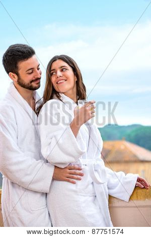 Couple In Bathrobe Standing On Hotel Balcony.