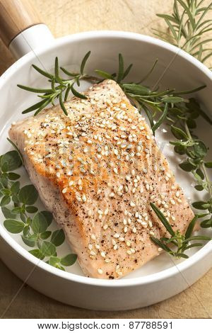 Salmon fillet with sesame seeds and herbs.  In white frypan.