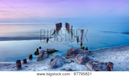 Old broken pier at sunset on the coast of the Baltic sea, Latvia poster