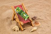 a deck chair with a euro banknote. photo icon for save on holiday and when traveling poster