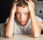 Sad boy at home. Unhappy abuse child. Emotions stress at teenager poster