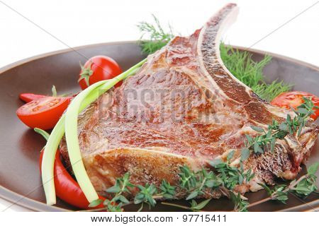 savory : roasted beef spare rib on dark dish with cutlery thyme pepper and tomato isolated over white background