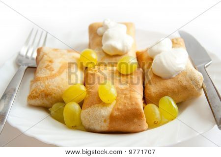 Pancakes With Filling On Plate With Sour Cream And Grapes