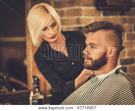 Client visiting hairstylist in barber shop poster