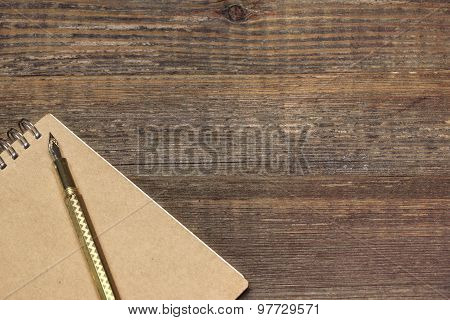 Notepad With Gold Fountain Pen On The Old Wood Table