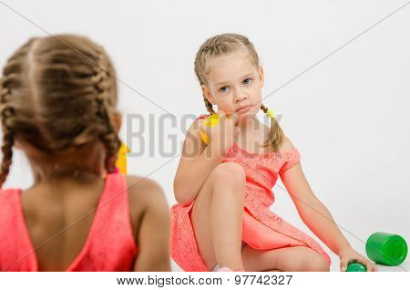 Girl Misunderstanding Looks At Her Sister While Playing With Toys