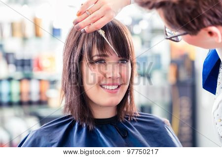 Hairdresser cutting woman hair in shop