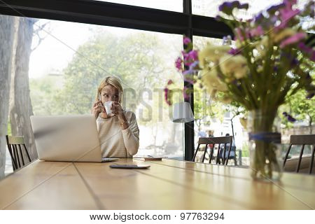 Confident business woman work on laptop computer holding the cup of cafe while talking on smartphone