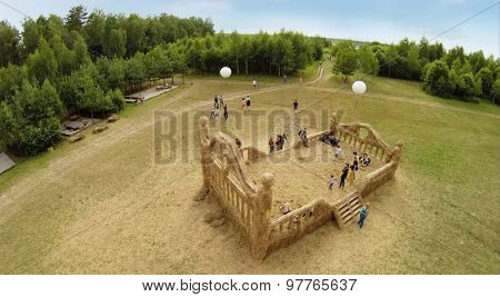 RUSSIA, NICOLA-LENIVETS - JUL 5, 2014: People get fun near big bed in Wonderland Park during 9th International Festival of landscape objects Archstoyanie. (Photo with noise from action camera)