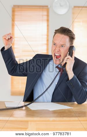 Furious businessman outraged on the phone in his office