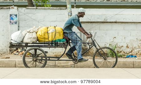 Man Riding His Customised Bicycle Fitted With A Loaded Trailer