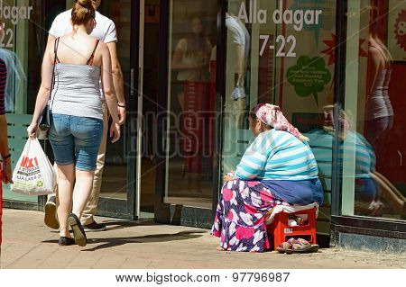 Beggar Outside A Shop