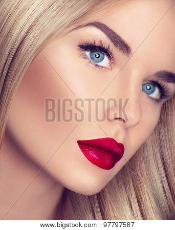 Beautiful Blonde Girl with Healthy blond Hair and perfect make up, beautiful skin. eye makeup, long eyelashes. Closeup of Beauty Woman face make up. Bright make-up with sexy red lips and perfect skin