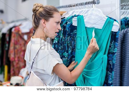 Shocked woman looking at price tag in clothing store