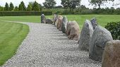 Way with erratic boulders in Jelling in Jutland Denmark. Jelling is part of the important archeological find places of Denmark. The historic ensemble of burial mounds church and rune-stones was declared as World Heritage by UNESCO. poster