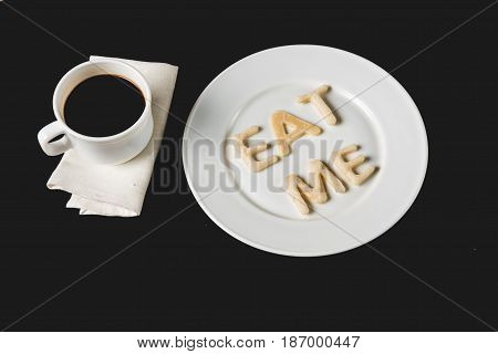 Top View Of Eat Me Lettering Made From Cookie Dough On Plate With Coffee Cup Isolated On Black