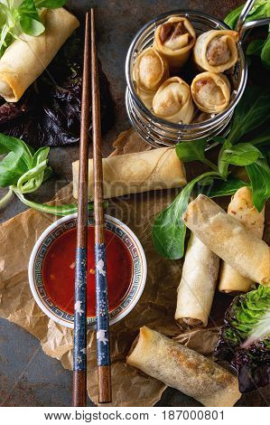 Fried spring rolls with red pepper sauce, served on crumpled paper and in fry basket with fresh green salad and wooden chopsticks over old metal texture background. Top view. Asian food