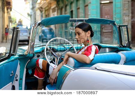 HAVANA CUBA - 11 DECEMBER 2016: The beautiful Cuban woman is getting the classical American car off in the centre of old Havana on Cuba