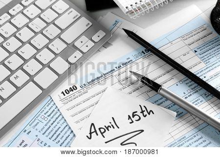 Paper note with text 15TH APRIL, forms and keyboard on table