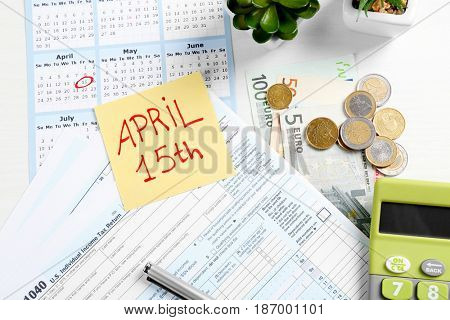 Paper note with text 15TH APRIL, forms and calculator on table