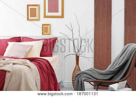 Comfortable bed with burgundy bedding in modern interior design