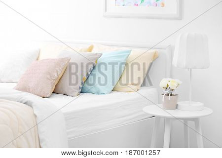 Comfortable bed with coverlet and pillows in light bedroom interior