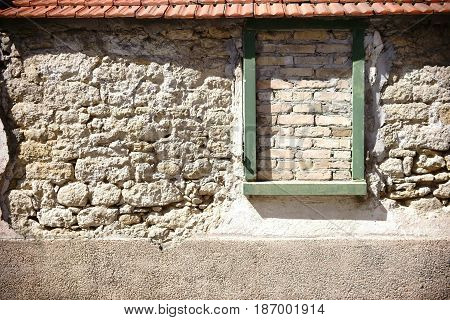 A rustic wall of staggered and broken stones with roof tiles and a walled window frame.