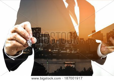 Businessman holding memo and prompt to write down. Double exposure, panoramic view contemporary megalopolis background, orange sun light