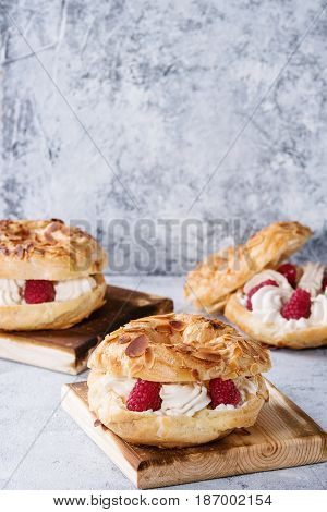Homemade choux pastry cake Paris Brest with raspberries, almond and rosemary, served on wooden serving board over gray blue texture background. French dessert