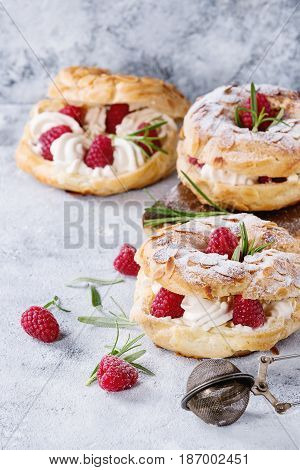 Homemade choux pastry cake Paris Brest with raspberries, almond, sugar powder and rosemary, served over gray blue texture background. Close up. French dessert