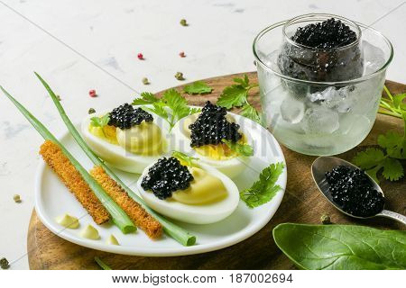 Appetizer Of Eggs, White Sauce And Black Caviar. Layout On A Wooden Background With Spices And Herbs