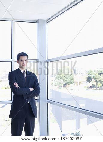 Asian businessman standing near office window