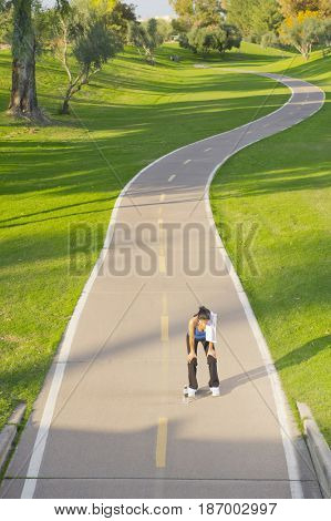 Hispanic woman stopping after exercise on path