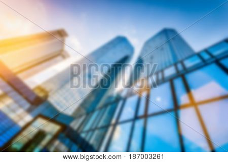 Abstract background blur bokeh image of modern skyscrapers in new business district in beautiful evening light at sunset with lens flare filter effect