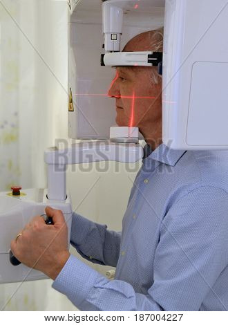 Patient doing panoramic teeth x-ray in dental clinic. Three dimensional teeth panoramic machine.